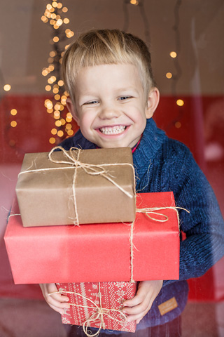 Young boy in blue sweater smiles as he carries Christmas presents
