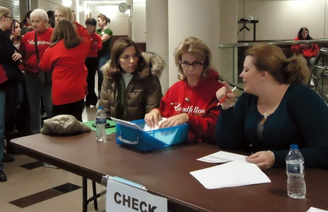 Three volunteers at the family check-in table