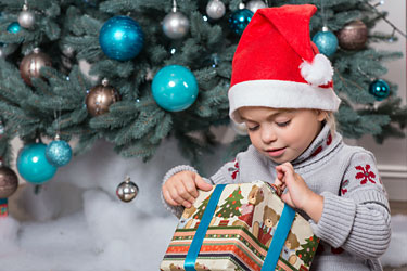 Young girl wearing Santa hat, sits on floor in front of Christmas tree, opening present