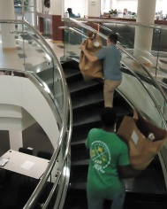 Volunteers climbing steps carrying bags of gifts and clothing