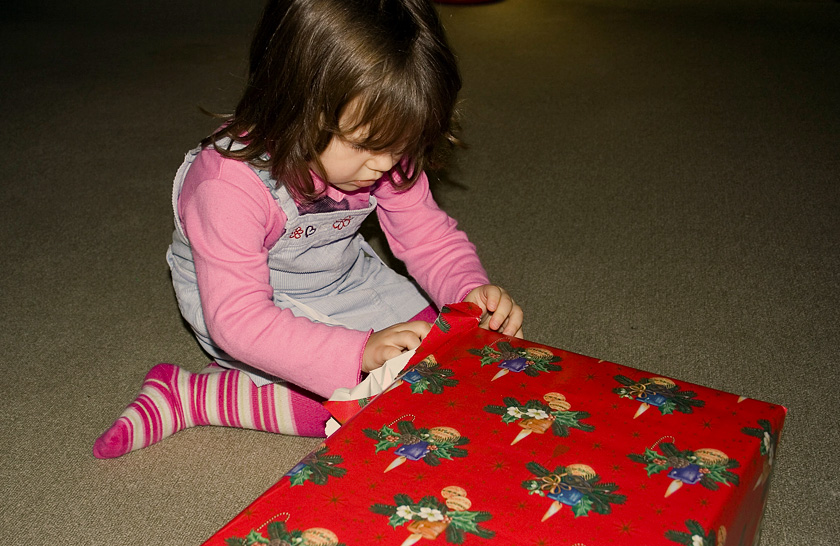 Young girl, sitting on the floor, opening Christmas present