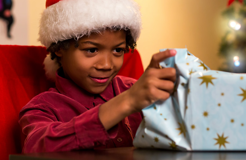 Boy wearing red Santa hat opening Christmas present